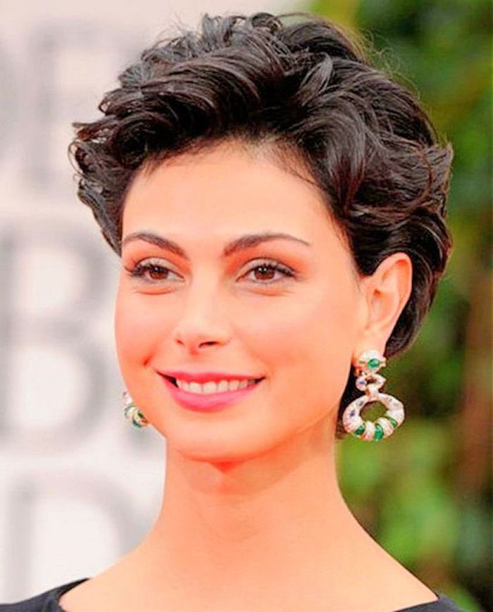 Ohrringe mit grünen Steinen von einer Frau, die Kurzhaarfrisur mit Locken hat