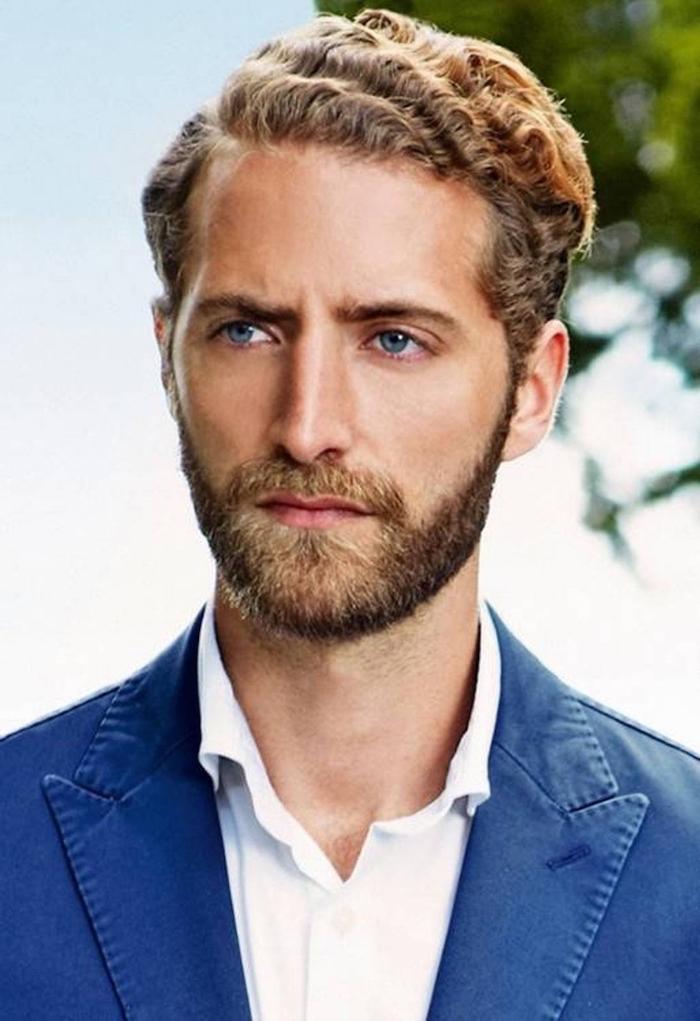 blonder Mann mit einem großen, gut gepflegten Bart, er hat lockige Kurzhaarfrisur