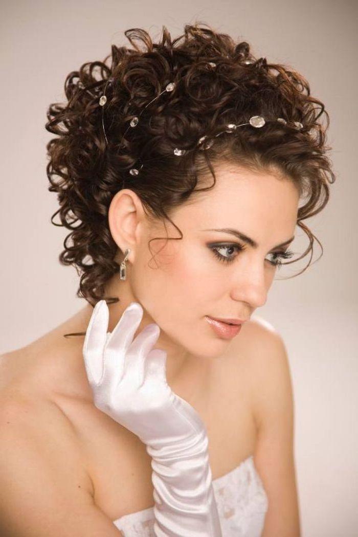 ein Braut, die lockige Kurzhaarfrisur anhat und mit Perlen das Haar geschmückt hat