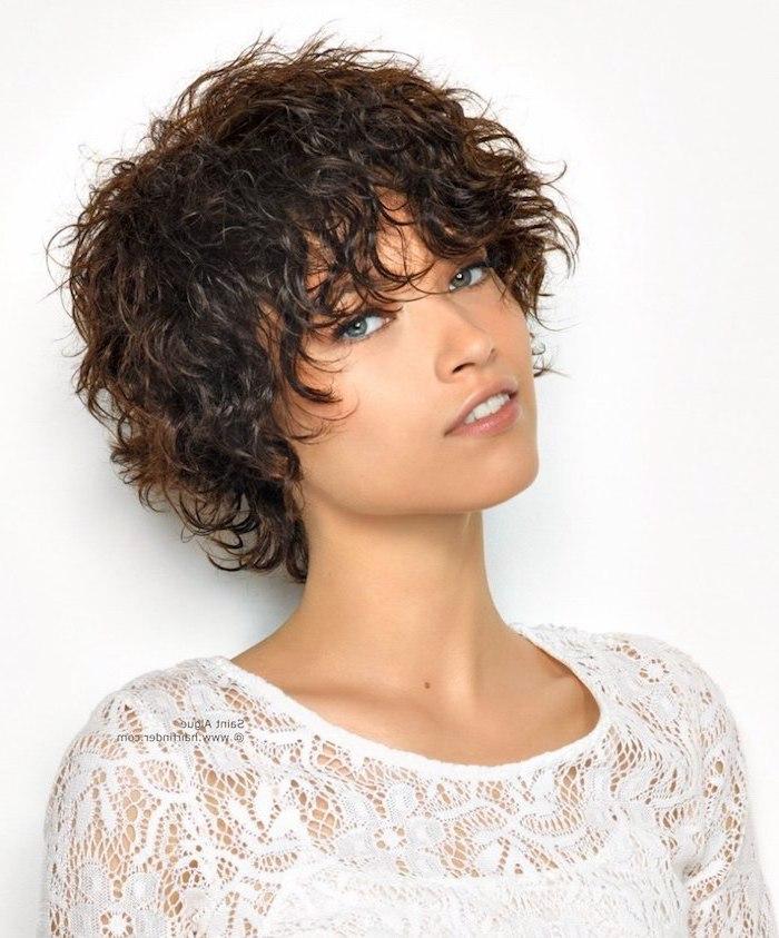 schöne Frau mit natürlicher Schminke und lockiger Kurzhaarfrisur von braunem Haar