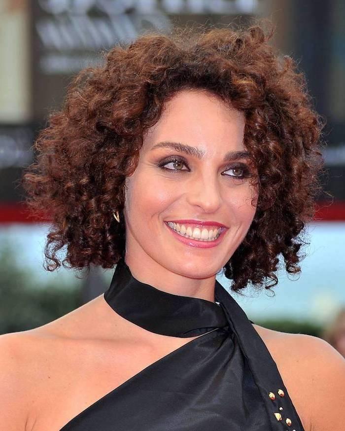 kurze braune Haare mit Locken von einer Star mit viel Schminke und schwarzem Kleid