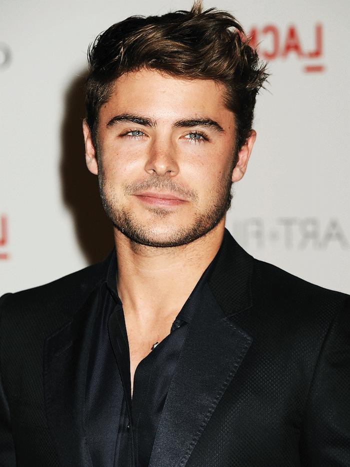 lockige Kurzhaarfrisuren von einem jungen hübschen Mann mit schwarzem Anzug