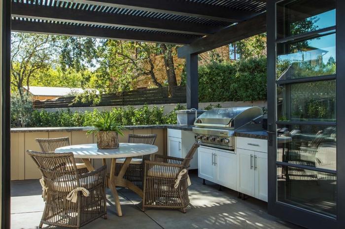 Sommerküche im Landhausstil, Rattanstühle und Holztisch, grüne Pflanzen