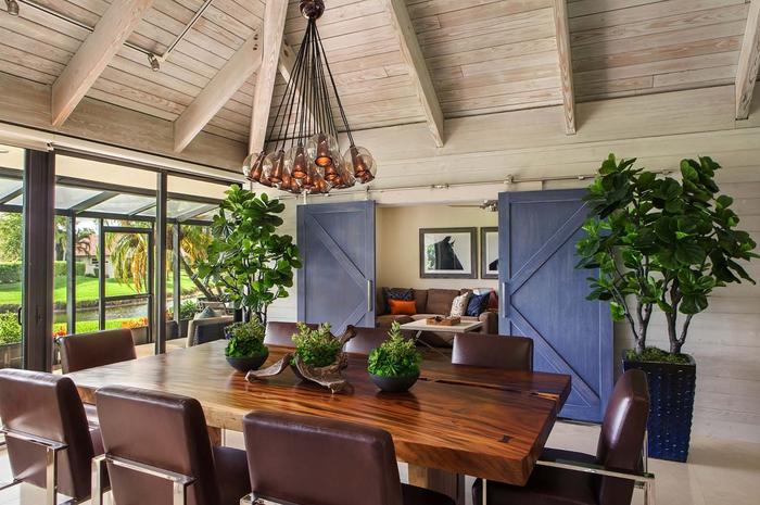 gemütliche Atmosphäre im Wohnzimmer schaffen, Leder- und Holzmöbel, große und kleine grüne Zimmerpflanzen, verspielter Kronleuchter