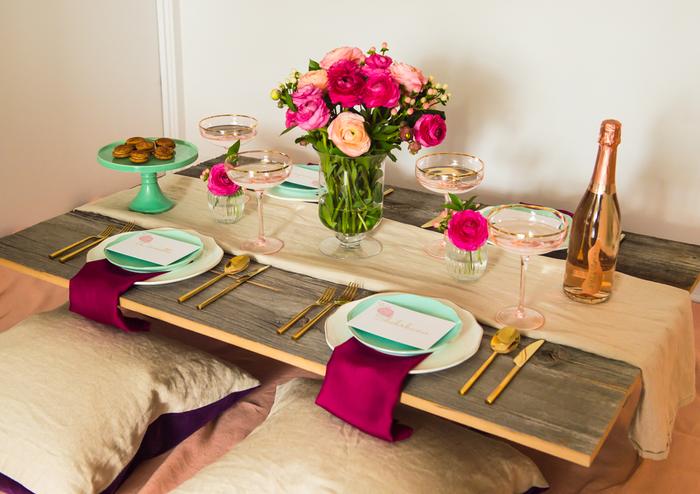 Landhausstil-Inspiration, Holztisch, Rosenstrauß in Glasvase, Pozellanteller, Sekt und französische Macarons