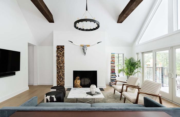 Wohnzimmer im Landhausstil einrichten, Hirschkopf an der Wand, Bücher- und Hölzerturm, verspielter Kronleuchter, Ledermöbel