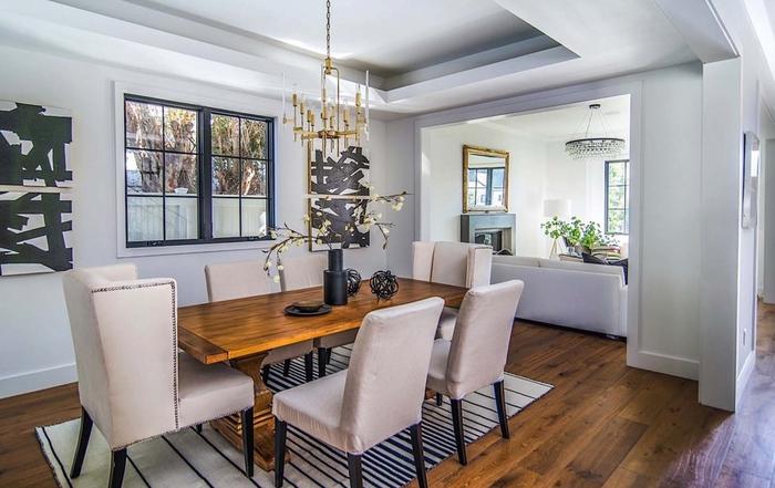 Wohnzimmer im Landhausstil einrichten, Holztisch und -Boden, Ledersessel, verspielter Kronleuchter