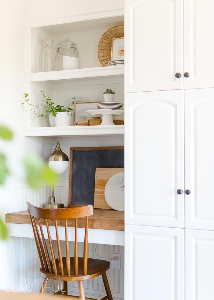 Einrichtung im Landhausstil, weiße Schränke und Regale, Vintage Holzstuhl, Porzellangeschirr