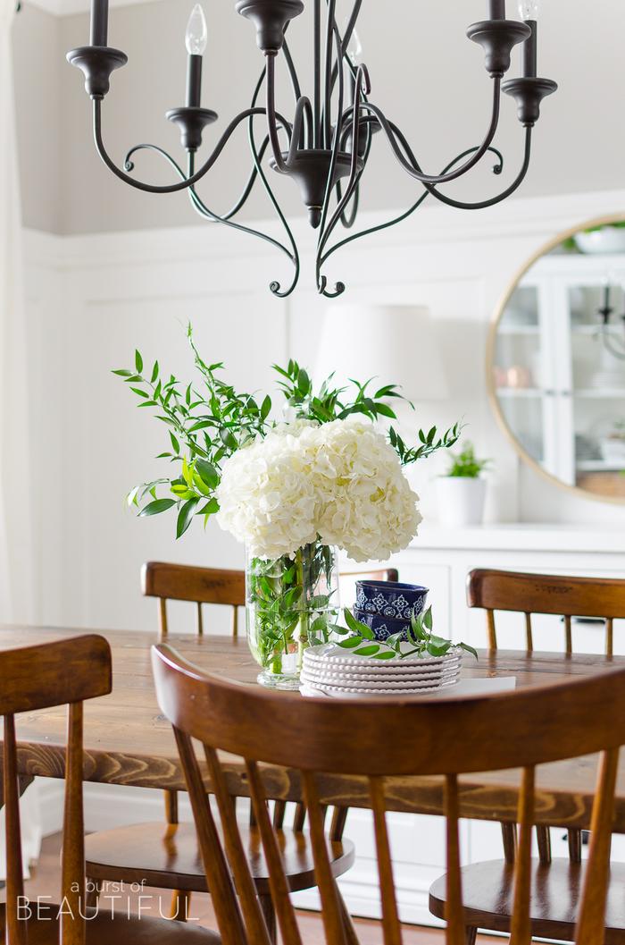Landhausstil-Inspiration, Holzmöbel, verspielter Kronleuchter, weißer Hortensienstrauss, Porzellangeschirr