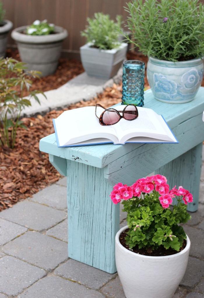 Garten im Landhausstil, blaue Holzbank, Blumentöpfe, geöffnetes Buch, Sonnenbrille darauf