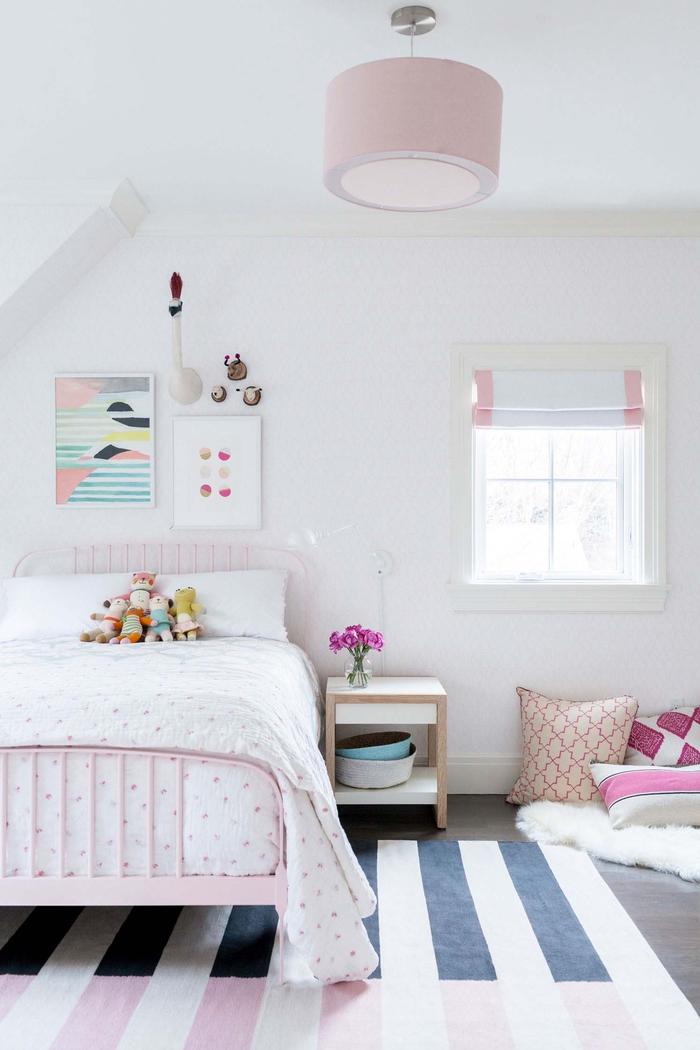Kinderzimmer in Pastelltönen, rosa Bett, kleine Kuscheltiere darauf, Dekokissen auf dem Boden, Blumenstrauss auf dem Nachttisch