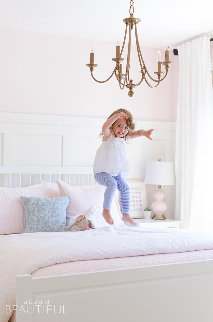 Schlafzimmer in Rosa, weißes Holzbett, verspielter Kronleuchter, süßes Kind springt auf dem Bett