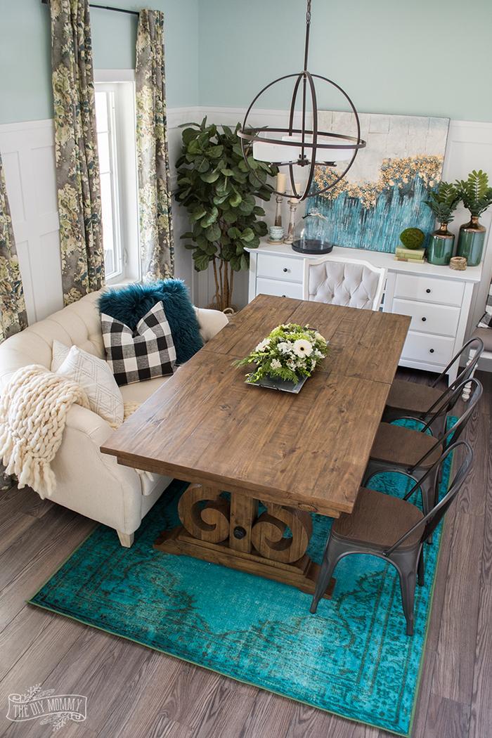 gemütliches Wohnzimmer im Landhausstil, massiver Holztisch, verspielter Kronleuchter, blauer Teppich, grüne Zimmerpflanzen, weiße Schrank und Sofa