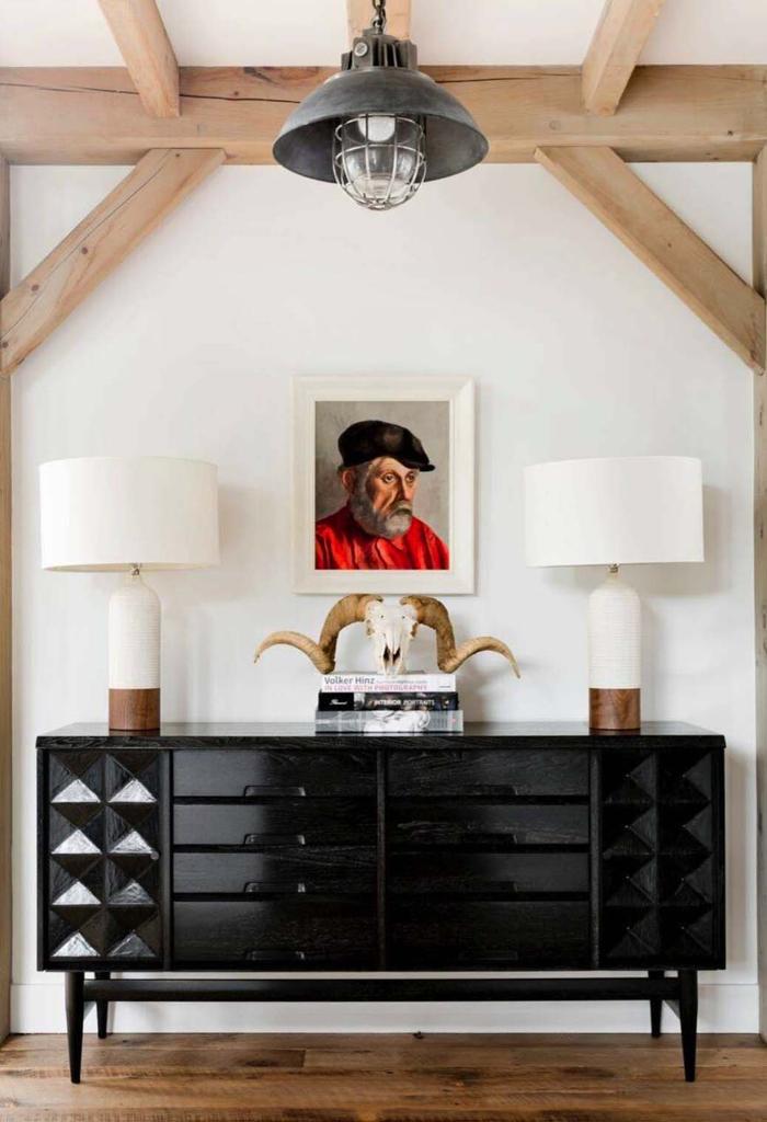 Wohnzimmer im Landhausstil, schwarze Kommode, zwei weiße Nachttischlampen, Hirschkopf, Gemälde