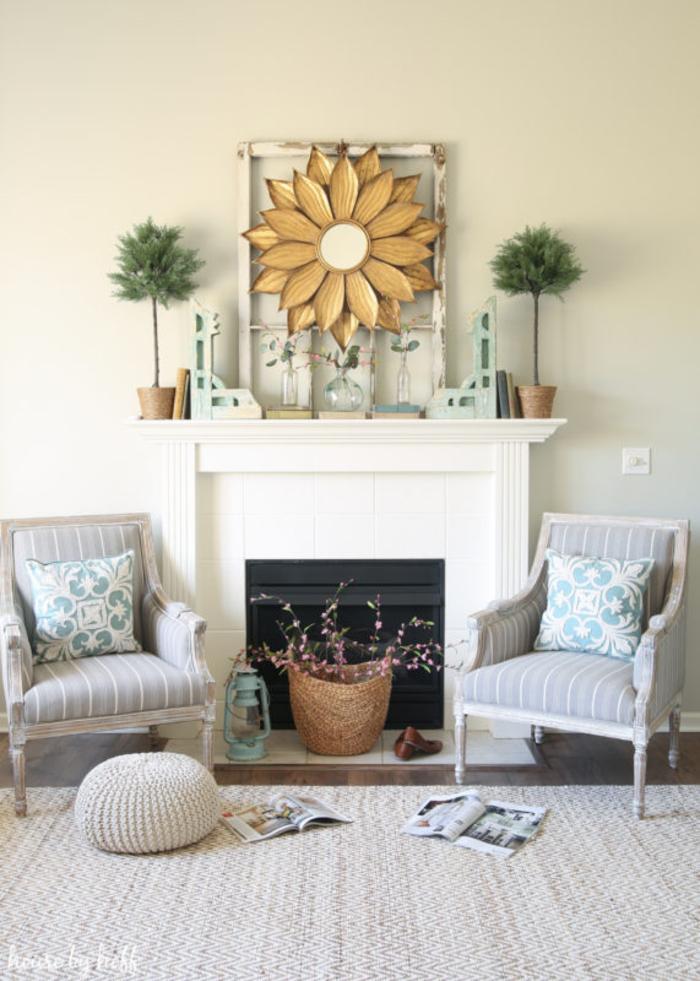 Wohnzimmer in zarten, hellen Farben, Kamin und zwei Sessel, Spiegel im Rahmen als Sonne, Rattankorb mit Blütenzweigen