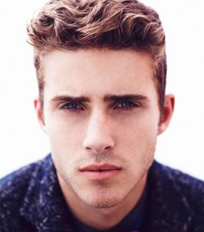ein hübscher junger Mann mit blauen Augen und Kurzhaarfrisur mit Locken, blau gekleidet
