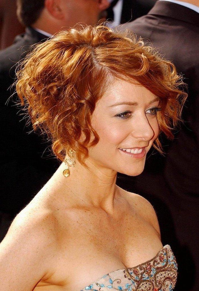 eine Schauspielerin mit Kurzhaarfrisur mit Locken, ihre Haare sind rot, sie trägt schöne Ohrringe