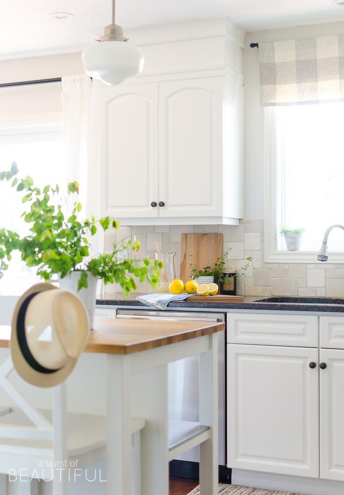 Küche im Landhausstil, weiße Holzmöbel, Limonade zubereiten, Sommerhut