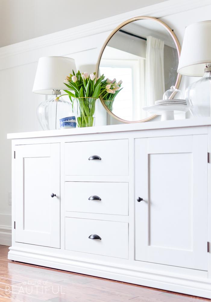 weißer Holzschrank, großer Spiegel, zwei Nachttischlampen, Tulpenstrauss in Glasvase