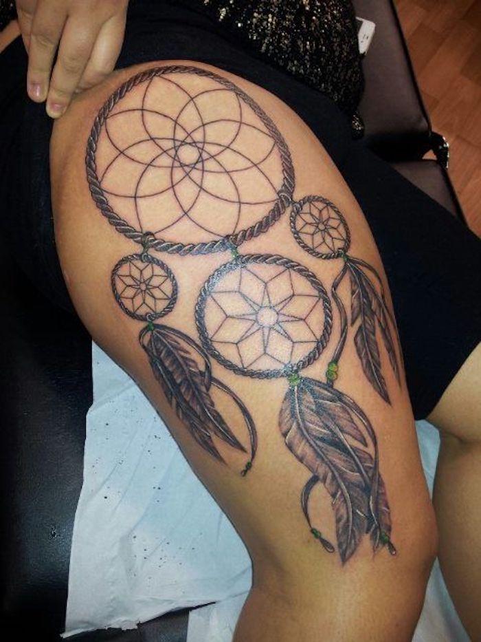 tattoo auf dem bein einer frau mit einem groüen schönen schwarzen traumfänger mit sternen und langen schwarzen federn