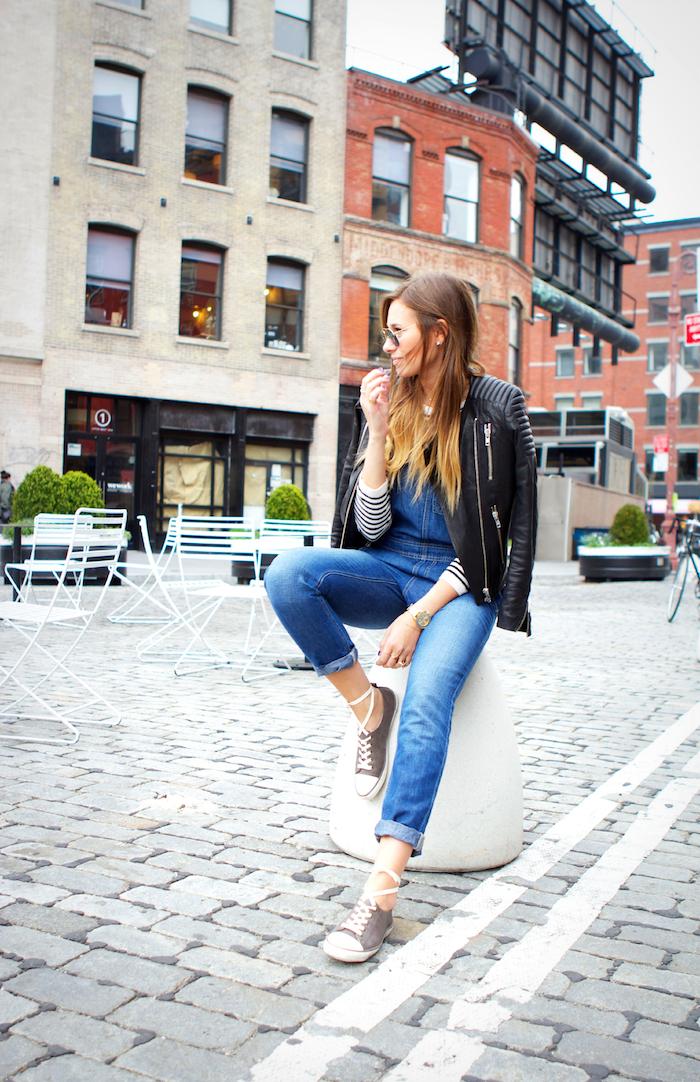 ombre blond model mit schöner frisur jeans sneakers lederjacke schwarz brille cafe