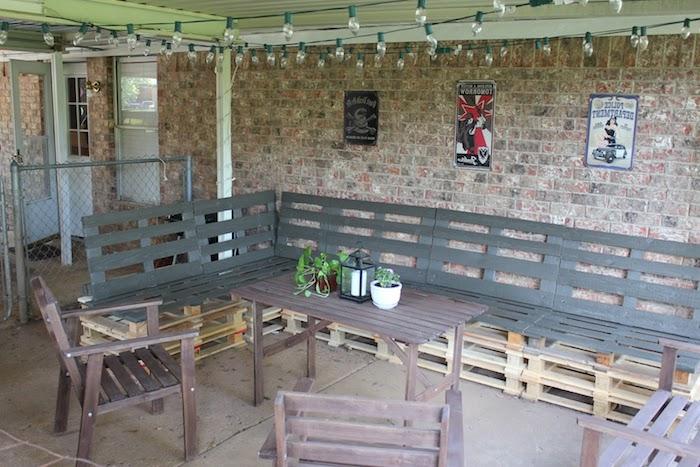 hier sind moderne stühle, ein tisch aus paletten und banken aus alten europalettem - idee für palettenmöbel für den außenbereich - ein tisch mit kleinen blumentöpfen und grünen pflanzen