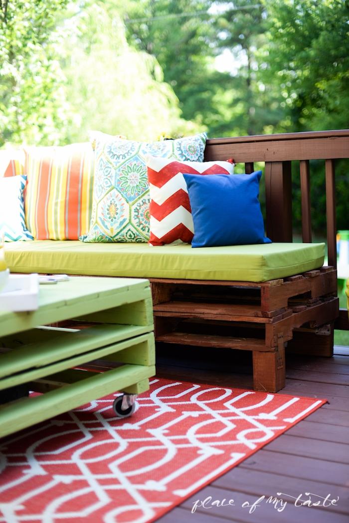 jetzt finden sie eine ganz tolle idee zum thema palettenmöbel terrasse - hier ist eine bank mit verschiedenen bunten kissen und ein tisch aus den alten europaletten und ein roter teppich