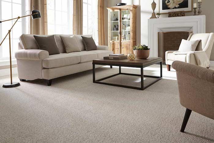 günstiger Bodenbelag grauer Teppich kleiner Tisch mit Dekorationen graue Couch ein Kamin