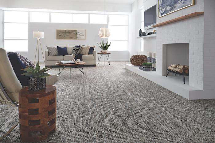 grauer Teppich in Streifen - ein weißes Sofa mit blauen Kissen - günstiger Bodenbelag