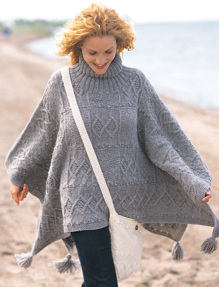 einen grauen Poncho, den das Mädchen am Strand trägt mit einer weißen Tüte - Poncho Damen Strick