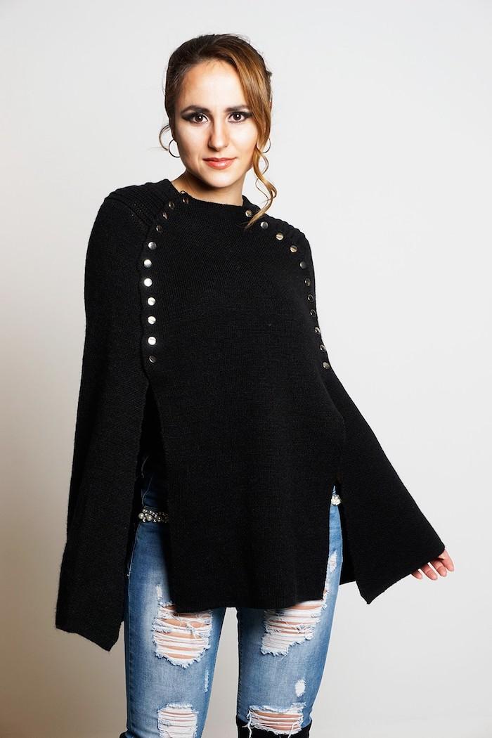 einen schwarzen Poncho mit vielen glänzenden Knöpfe und modernen Jeans - Häkelponcho
