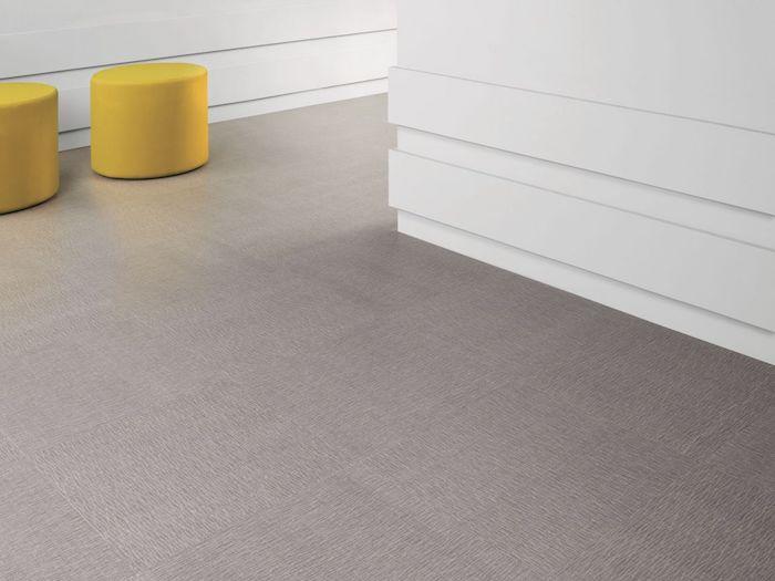 eine Ecke mit PVC Boden zwei gelbe Hocker lila Boden und weiße Wände im Flur