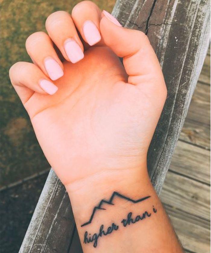 eine gebrochene Linie in der Form von Gebirge und Tattoo Schriftzüge am Handgelenk