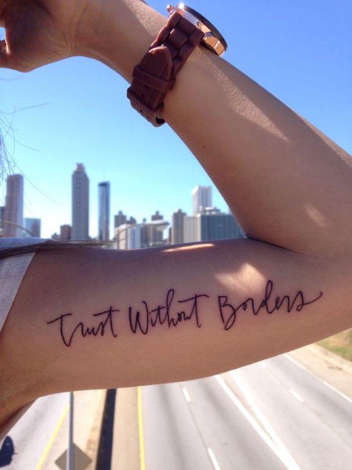Schrift Tattoo am Oberarm eine Uhr eine Hand mit Muskel ein weiser Spruch