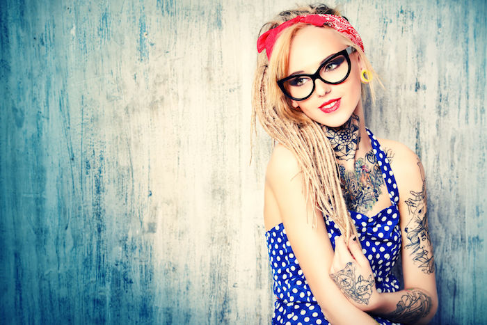 tattoo motive, rockabilly frisur, blonde lange haare, dunkelbraues kleid mit weißen punkten
