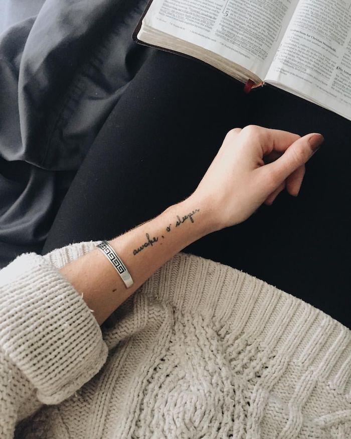 Tattoo in feiner Schreibschrift am Handgelenk, Frauen Tattoos, lässiges Outfit, weißer Pulli und schwarze Hose, silbernes Armband