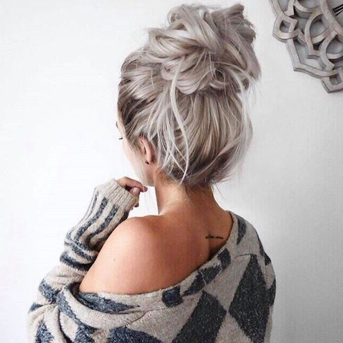 silbernes haar, lässige dutt-frisur, beige bluse mit blauen geometrischen elementen