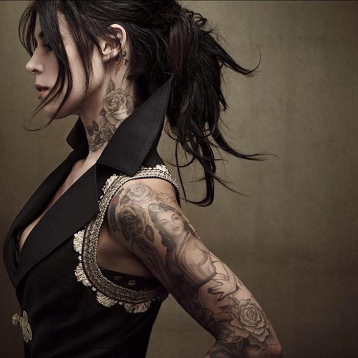tattoo arm frau, dame mit schwarzen hochgesteckten haaren und vielen tattoos