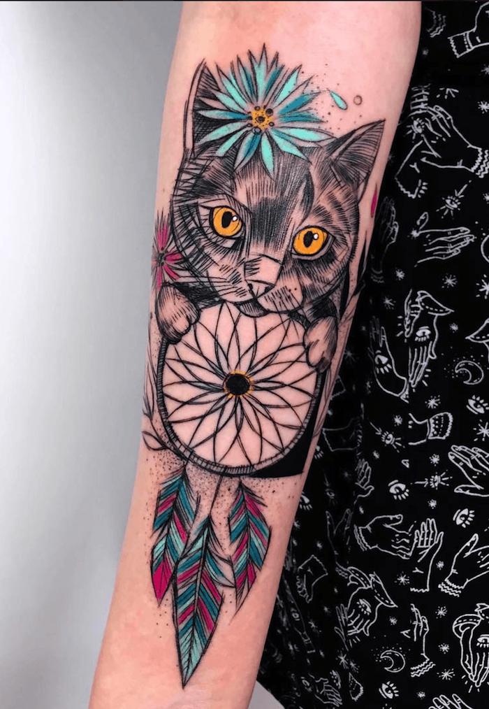 Traumfänger Tattoo mit Katze am Unterarm, farbige Federn und Blumen, Tattoo Ideen für Frauen