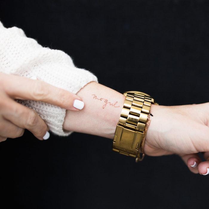 Kleines Tattoo in Schreibschrift am Handgelenk, weißer Nagellack, goldene Uhr, weißer Pulli