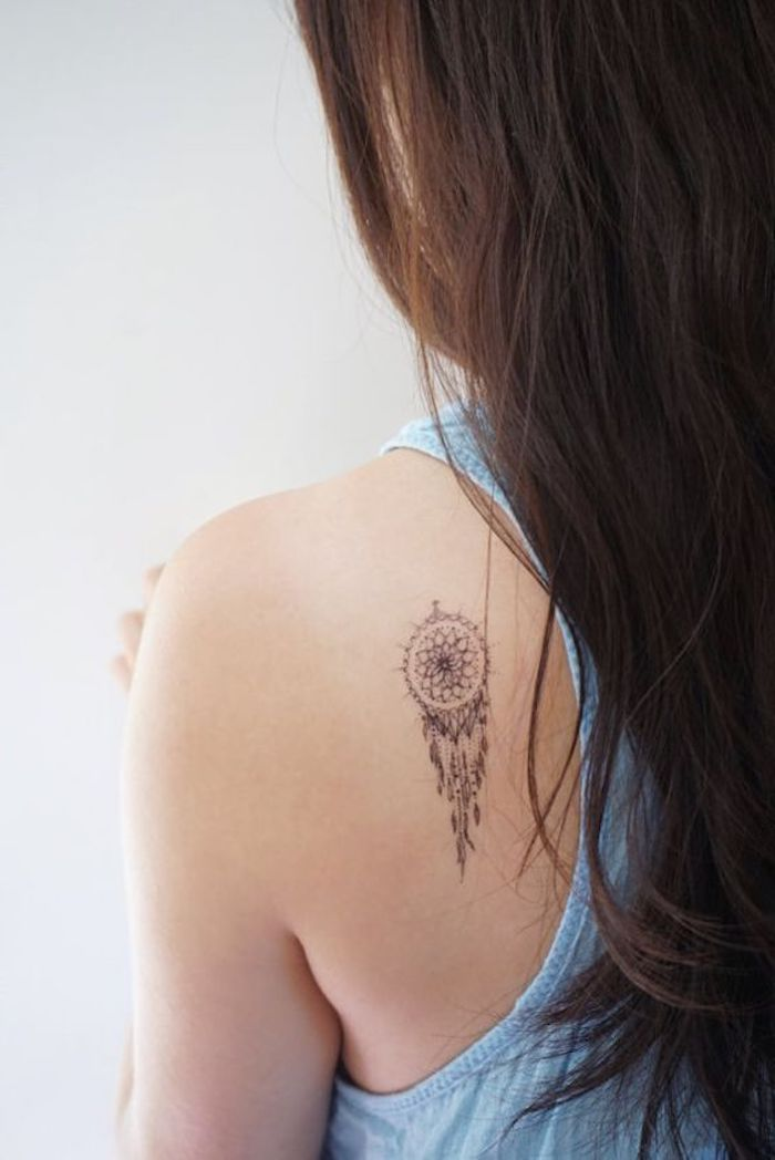 Traumfänger Tattoo am Rücken, blaues Top, lange offene dunkelbraune Haare