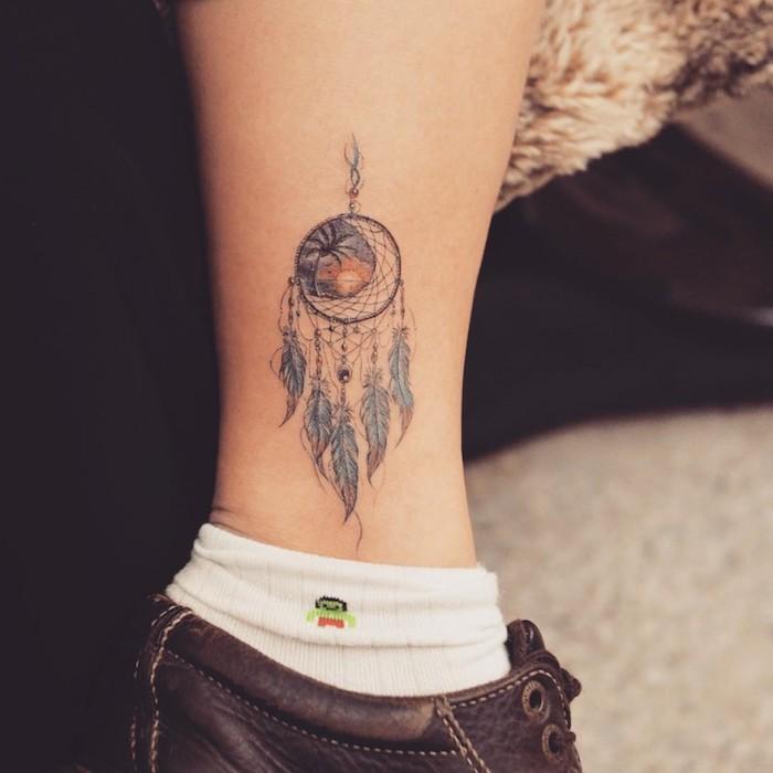 Traumfänger Tattoo an der Wade, blaue Federn und Perlen, Sonnenuntergang am Meer und Palme