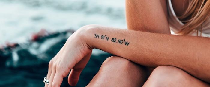 Mittelgroßes Tattoo am Unterarm, sich GPS Koordinaten eines Lieblingsorts tätowieren lassen