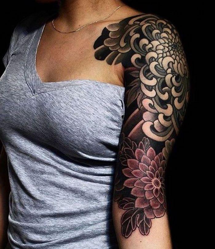 tattoo arm frau, dame mit grauer bluse und großer oberarm tätowierung