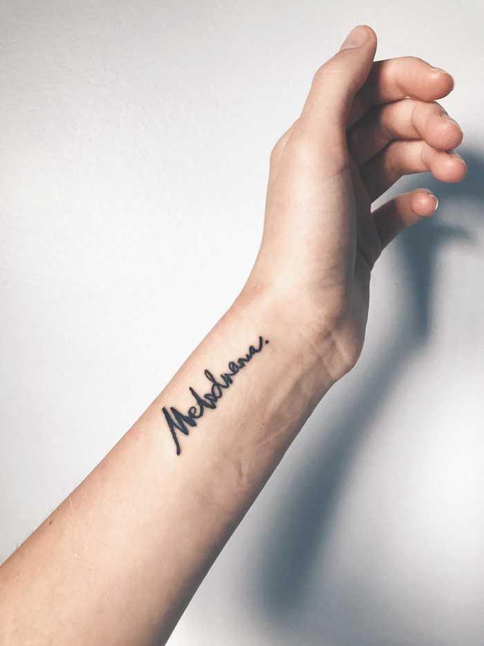Mittelgroßes Tattoo am Handgelenk, Tattoo in Schreibschrift, sich den Namen eines Lieblingsmenschen tätowieren lassen