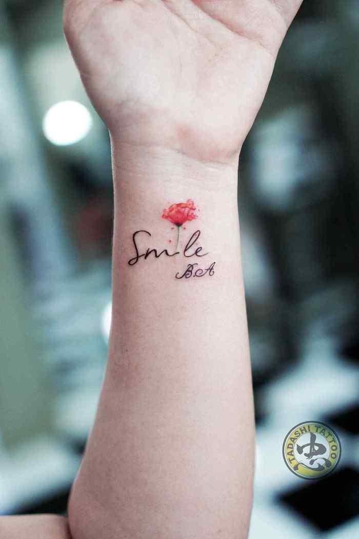 Kleines Tattoo am Handgelenk, Smile Tattoo in Schreibschrift und kleine rote Rose