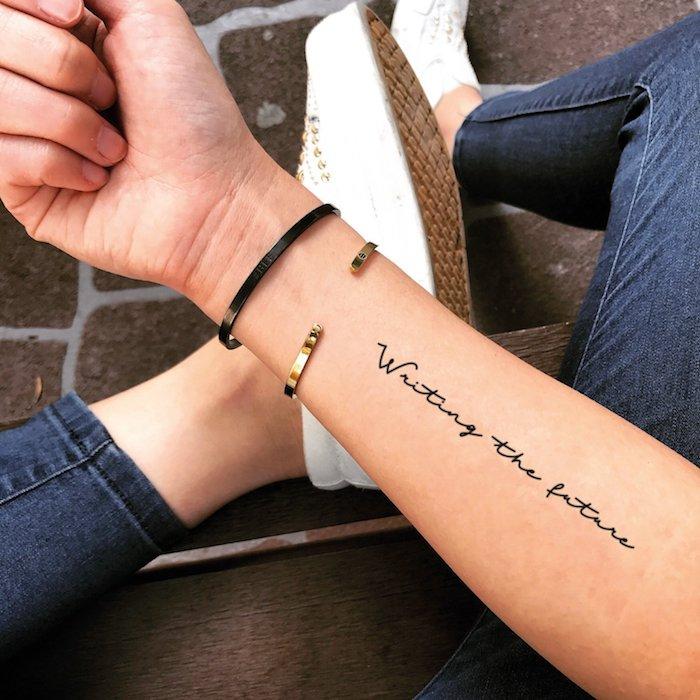 Mittelgroßes Tattoo am Unterarm, Writing the future, Tattoo in feiner Schreibschrift
