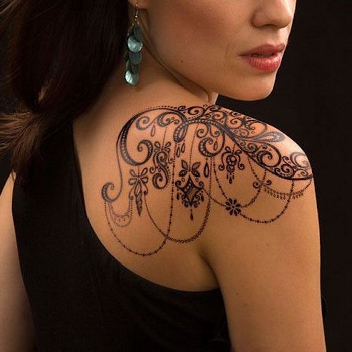 tattoo schulter, schwarzes abendkleid, blaue ohrringe