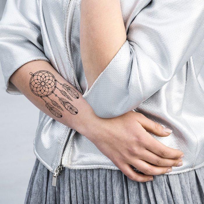 Dreamcatcher Tattoo am Unterarm, Tattoo Motive mit Bedeutung, silberner Blazer, grauer Rock