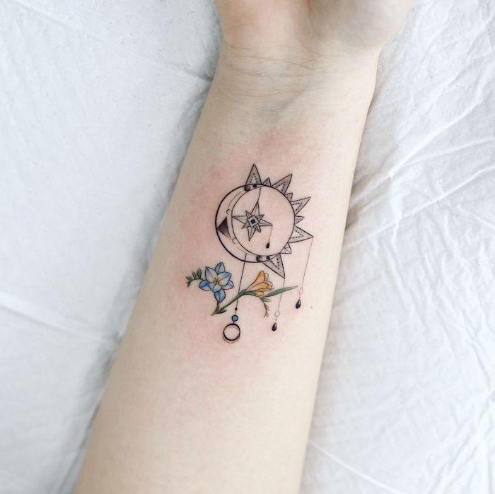 Traumfänger Tattoo am Unterarm, Halbmond und Sonne, blaue und gelbe Blumen, Stern in der Mitte